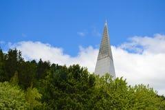 Bosque, cielo azul y el edificio conmemorativo en la ciudad de Khanty-Mansiysk, Rusia fotos de archivo