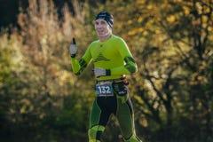 Bosque corriente del otoño del atleta de mediana edad del hombre en ropa de la compresión Imagenes de archivo