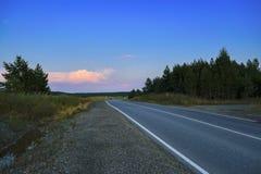 Bosque del oto?o con la carretera nacional en la puesta del sol Paisaje colorido con los ?rboles, camino rural, sol en ca?da foto de archivo libre de regalías