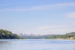 Bosque en los bancos del río Zona industrial de una ciudad Imágenes de archivo libres de regalías