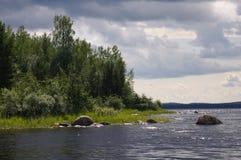 Bosque hermoso, lago y cantos rodados enormes Imagen de archivo
