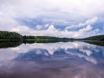Bosque y nubes reflejados en el lago Imágenes de archivo libres de regalías
