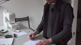 Bosquejo creativo del dibujo del diseñador de moda del hombre en taller de costura almacen de metraje de vídeo
