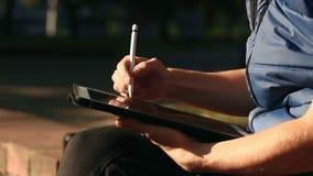 Bosquejo de Drawing del diseñador en la tableta usando la aguja en el parque almacen de video