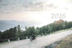 Bosquejo de la motocicleta del paseo del hombre en la montaña y buscar 2016 Años Nuevos Imágenes de archivo libres de regalías