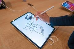 Bosquejo del dibujo de la muchacha del diseñador gráfico en la pantalla digital de la tableta con el lápiz de la aguja imagen de archivo libre de regalías