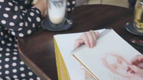 Bosquejo modelo femenino del dibujo del artista en el café almacen de video