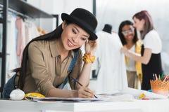 Bosquejos asiáticos sonrientes del dibujo del diseñador de moda mientras que colegas que trabajan detrás Fotos de archivo libres de regalías