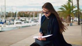 Bosquejos de dibujo de la mujer en su sketchbook al aire libre Palmas y yates en fondo almacen de metraje de vídeo