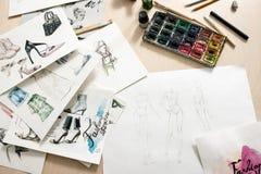 Bosquejos de la moda en el escritorio del diseñador Imagen de archivo libre de regalías