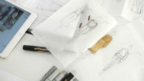 Bosquejos de la ropa, dibujados en las hojas de papel almacen de video