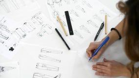 Bosquejos de la ropa, dibujados en las hojas de papel metrajes