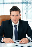 Boss. Young business executive sitting in chaire attentively looking at you Royalty Free Stock Photos