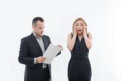 Boss angry with young employee. Angry boss businessman with blank paper and embarrassed young attractive women employee holding her head and looking at camera Royalty Free Stock Image