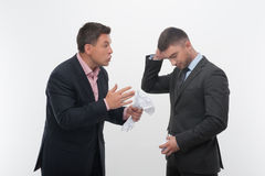 Boss angry with young employee. Senior and junior business people in elegant suits. Boss angry with employee looking down, holding crumpled paper isolated on Stock Photo