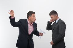 Boss angry with young employee. Senior and junior business people in elegant suits. Boss angry with employee looking down, holding crumpled paper isolated on Stock Image
