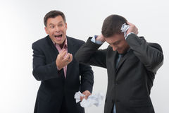 Boss angry with young employee. Senior and junior business people, boss angry with young handsome employee holding hands to ears with crumpled paper isolated on Stock Image