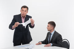 Boss angry with young employee sitting at desk Stock Photos