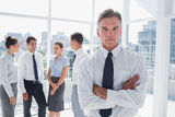 Boss with arms folded standing in a modern office Royalty Free Stock Photography