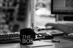 The boss. Black and white picture of a cup of coffee, pen and a keyboard on the boss's working desk in the early morning Royalty Free Stock Images