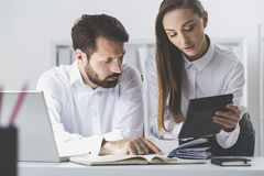 Boss with book and secretary with calculator Stock Images
