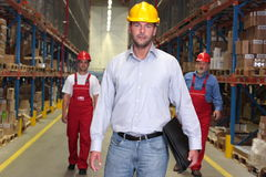Boss with briefcase at the front of workforce. Boss with briefcase at the front of team of workforce in warehouse -2 workers in background royalty free stock photo