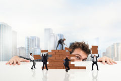 Boss builds a business team. Businessman watches a teamwork of businesspeople work together by building a brick wall royalty free stock photo
