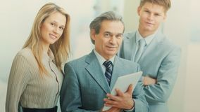 Boss with digital tablet and his business team. Boss and business team on office background standing in a wedge behind the leader Royalty Free Stock Image