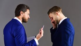 Boss checks paperwork near tired employee. Businessmen assess th. E terms of the deal. Business contracts concept. Men in suit or businessmen with document or royalty free stock photography