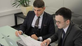 The boss checks the report of his junior subordinate in his office. The professional in three-piece suit and tie looks at the paper with the charts in his hand stock video