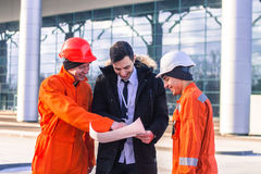 Boss or Chief  instructs young team of  young engineers. With a construction project. They wear overalls and safety helmets. Business modern background Royalty Free Stock Image