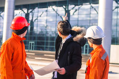 Boss or Chief  instructs young team of  young engineers. With a construction project. They wear overalls and safety helmets. Business modern background Royalty Free Stock Images
