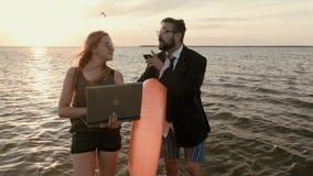 Boss con una secretaria de la muchacha en un traje y ningunos pantalones, en la rodilla en el agua metrajes