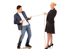 Boss concept-woman holding rope in two fingers, man pulling a rope and can't win Royalty Free Stock Photos