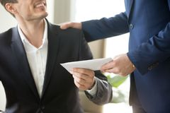 Boss congratulating employee with getting reward. Company leader giving money bonus in paper envelope to happy smiling office worker, congratulating employee Stock Image