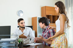 Boss and couple talking with grave countenances in the office Royalty Free Stock Photos