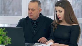 Boss de la edad del retiro con el trabajador de sexo femenino que usa el ordenador portátil que se sienta en la tabla en la ofici almacen de video