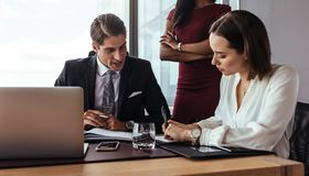Boss dictating to assistant at office. Business people working in team at office. Three people in office with businessman dictating to his assistant making notes Royalty Free Stock Image