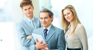 Boss with digital tablet and his business team. Boss and business team on office background standing in a wedge behind the leader Royalty Free Stock Photography