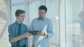 Boss discuss project with employee, gives advice, using digital tablet in new modern office. stock video footage