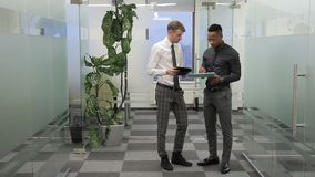 The boss discuss the report with the manager standing in the corridor of modern office. The businessman wears tie and holds the tablet during the converstion stock video footage