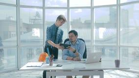 Boss discute proyecto con el empleado, da consejo, usando la tableta digital en nueva oficina moderna almacen de video