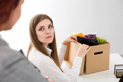 Boss dismissing an employee. Dejected fired office worker looking at her boss and packs her belongings to carton box. Getting fired concept Stock Photography