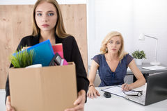 Boss dismissing an employee. Getting fired concept. Boss dismissing an employee. Dejected fired office worker carrying a box full of belongings. Getting fired Royalty Free Stock Photos