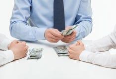 Boss dividing money among collaborators Stock Photo
