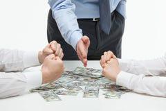Boss dividing money among collaborators Royalty Free Stock Image