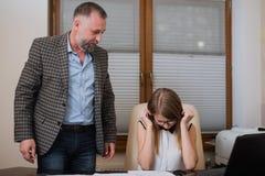 Boss está enojado de empleado El oficinista incurrió en una equivocación foto de archivo