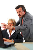 Boss Is Explaining. A senior businesswoman in her fifties is working on a laptop in an office and seems to be shocked. Her boss behind her is angry. Isolated Stock Image