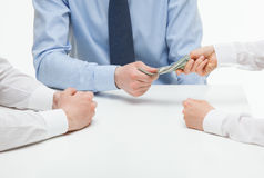 Boss giving dollars to collaborator Stock Photos