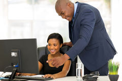 Boss guiding employee. Friendly african boss guiding his new employee with her work Stock Images